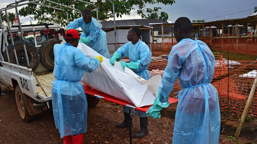 Sierra Leone government burial team members load the body of an Ebola victim onto a truck at an MSF facility in Kailahun, on August 14, 2014.