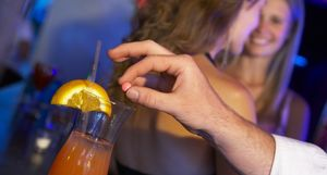 Man's hand drugging woman's drink