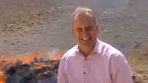 BBC reporter standing next to burning pile of drugs too high to finish report
