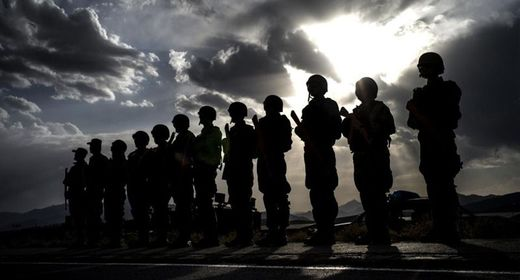 Afghan policemen stand guard