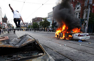 Protester jumps on burnt-out police care