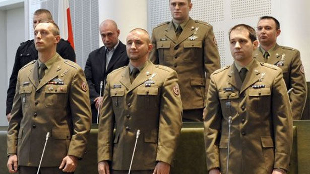 Four Polish soldiers, accused of committing war crimes in Afghanistan, on Wednesday faced the first day of a re-trial after Poland's Supreme Court last year overturned their acquittal, a military court spokesman said.