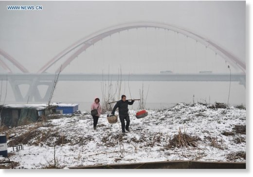Citizens walk on the snow-covered bank of the Xiangjiang River in Changsha, capital of central China's Hunan Province, Feb. 1, 2016