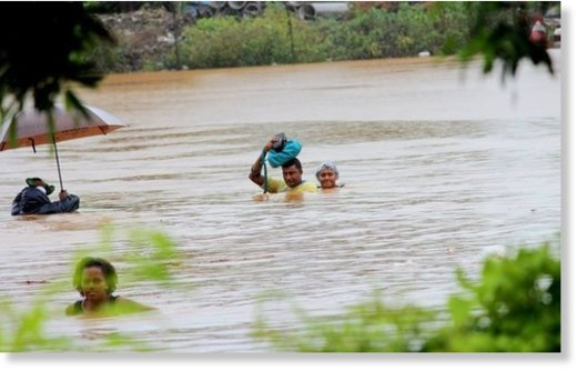 Residents of Korociri cross the flooded Nadi Back Road