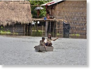 Children use a boat in a village near Kaziranga National Park. seven people have died so far in the floods affecting the state.