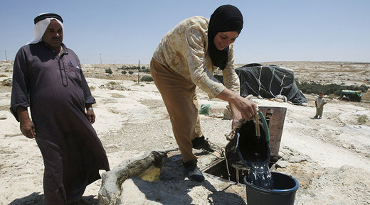 Palestinians getting water from well
