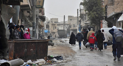 Syrian residents fleeing eastern part of Aleppo walk through a street in Masaken Hanano, a former rebel-held disctrict which was retaken by the govt forces last week