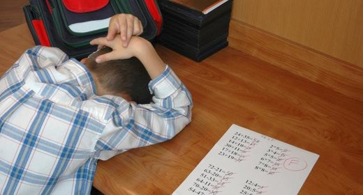 young boy hangs his head in shame after getting an F on his math test