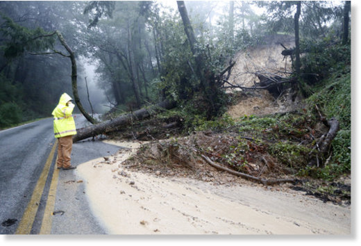 A Santa Clara County Roads and Airport Department worker responds to the scene of downed tree and mudslide on Summit Road in the Santa Cruz Mountains, Calif., Sunday, Jan. 8, 2017.