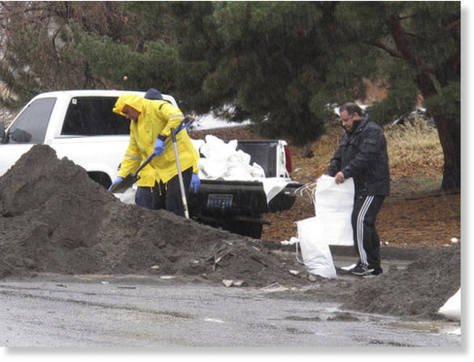 Local residents braved the heavy rain to fill sandbags on Sunday, Jan. 8, 2017, near the Truckee River in Sparks, Nev.