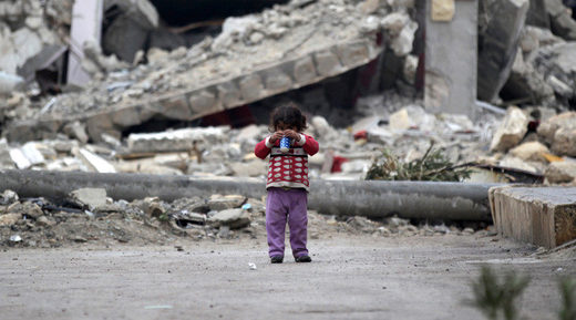 girl plays near rubble of damaged buildings in al-Rai town, northern Aleppo