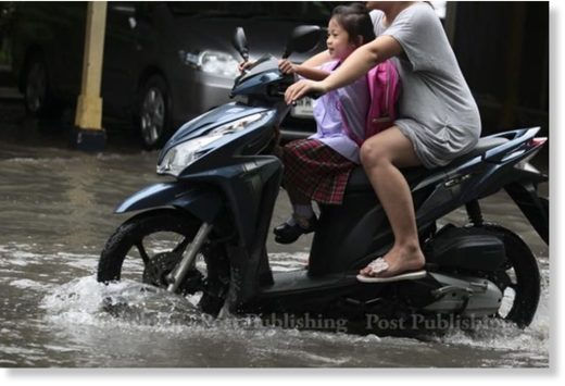 A mother and her daughter ride through a flooded street by to get to school. Many areas of Bangkok were flooded following heavy rain in the early hours.