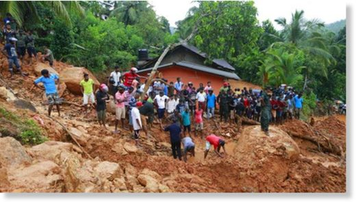 Sri Lankans watch military rescue efforts at the site of a landslide in Bellana village in Kalutara district, Sri Lanka, Friday, May 26, 2017.
