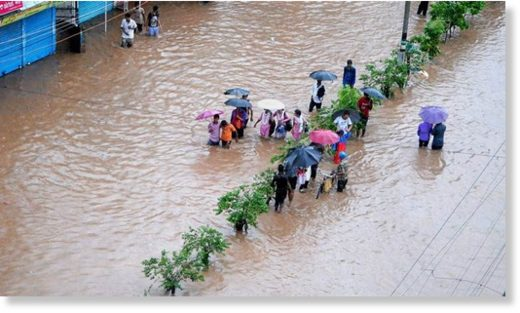 People make their way through a flooded street after heavy rainfall in Guwahati, Assam on Tuesday.