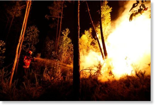 Firefighters work to put out a forest fire near Bouca, in central Portugal