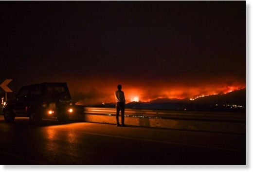 A man stands on the roadside watching a wildfire at Anciao, Leiria