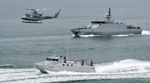Indonesia navy soldiers on warship and helicopter are seen during the launch of coordinated patrols to beef up security