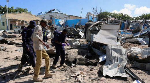 Somali policemen assess the scene of an attack on a government building in Mogadishu