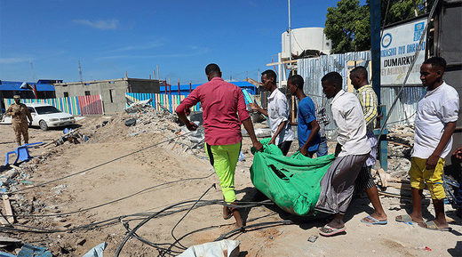 Civilians carry the dead body of an unidentified man killed during an attack on a government building in Mogadishu