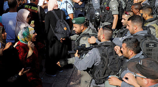 Palestinian woman argues with an Israeli border policeman