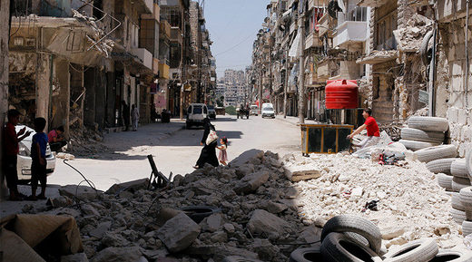 A woman walks with a child amid rubble at Bustan al-Qasr neighbourhood in Aleppo
