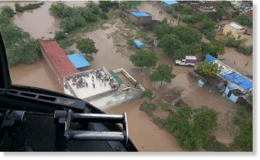 Flood victims, including a patient needing kidney dialysis, await an airlift from a rooftop in Abiyana village, Gujarat after monsoon floods hit