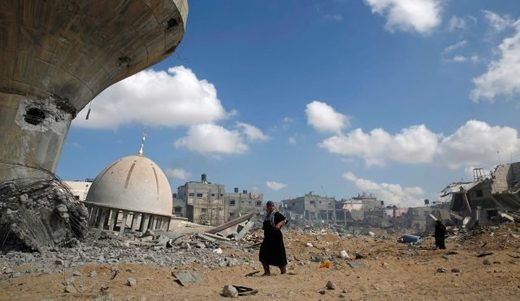 Palestinian women walk past a mosque and water tower damaged by Israeli air strikes