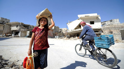A girl is seen at a damaged site in Aleppo's Sheikh Maqsoud neighbourhood, Syria
