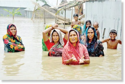 Desperate for help, a group of women and children at Hotathpara village in Fulchhari upazila, Gaibandha wade through chest-high water to get to relief workers on August 16, 2017.