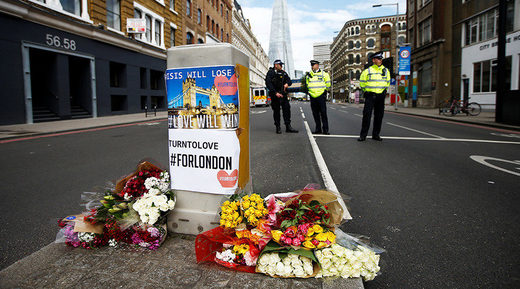 Flowers and messages lie behind police cordon tape near Borough Market, London