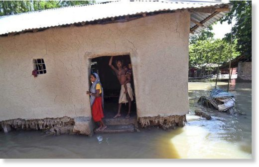 Villagers stand inside their house destroyed by floodwaters at Katihar district, in the eastern Indian state of Bihar, on Saturday 19 August 2017.