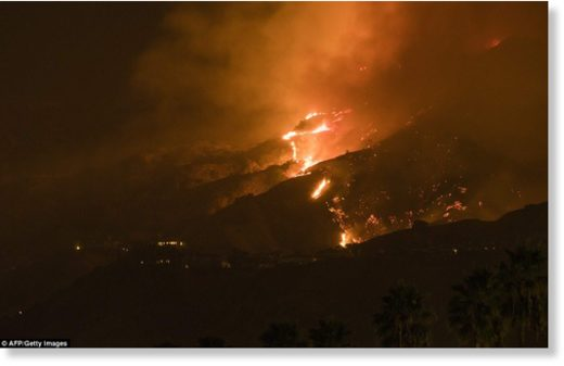 The La Tuna Canyon fire burns in the hills above Burbank early Saturday as the fire marches along hillsides