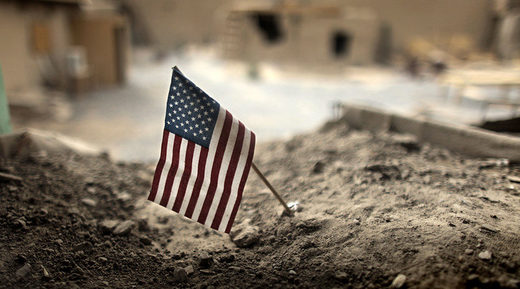 An American flag is placed in a dirt-filled barrier, at Combat Outpost Nolen, north of Kandahar