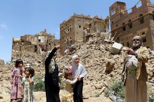 People stand in front of houses destroyed by Saudi-led air strikes in the Yemeni city of Saada () War Saudi Arabia