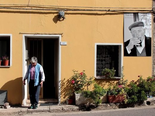A resident of Seulo, Italy, leaves a home that is adorned with a black-and-white photo of a centenarian who previously lived there.