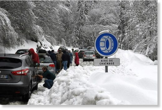 Snow made some roads impassable in the French Alps and forced these motorists to put chains on their wheels