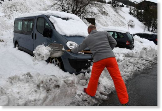 A man shovels snow in Les Menuires, France, on January 4