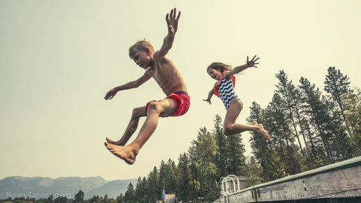 children jump off dock swimming