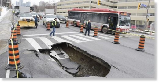 City work crews attend at the scene of a sinkhole in the southbound lanes of Yonge St., just south of Highway 401, at William Carson Cres