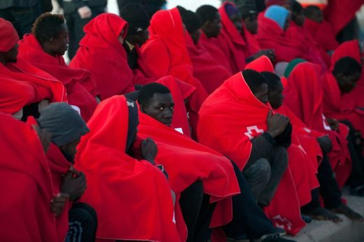 Migrants keep warm with Red Cross blankets after arriving aboard a coast guard boat at Malaga's harbour on December 7, 2017