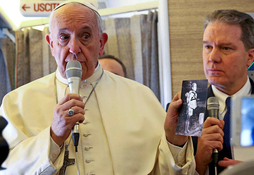 Pope Francis holds a picture depicting a victim of the 1945 atomic bombing in Nagasaki as he speaks to reporters onboard the plane for his trip to Chile and Peru January 15, 2018