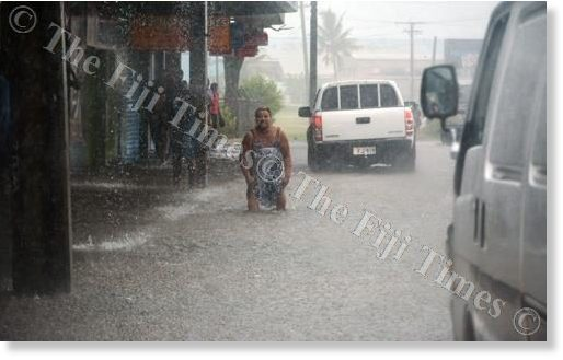 A woman is seen wading in the flooded Vitogo Pde in Lautoka City yesterday.