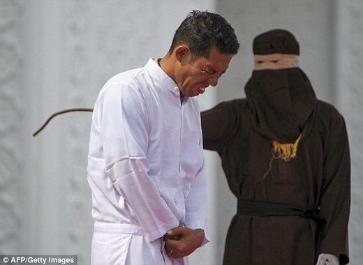 Jono Simbolon (front), an Indonesian Christian, grimaces in pain as he is flogged in front of a crowd outside a mosque in Banda Aceh, Aceh province, on January 19, 2018