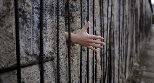 hand through remains of Berlin Wall