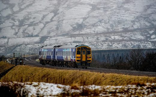 A steam train passes over Ribblehead Viaduct in North Yorkshire as snow covers the landscape