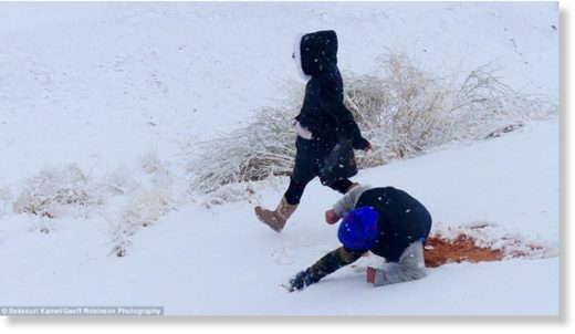 Snowday! A child takes a tumble in the snow, exposing the red sand hidden underneath it