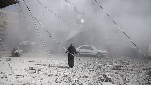 A woman gestures as she walks on rubble of damaged buildings