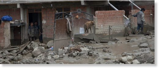 Rocks and mud clog a street outside a flooded home, where a couple and a dog stand by, after a river overflowed in Tiquipaya near Cochabamba, Bolivia, Wednesday, Feb. 7