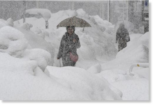 A woman walks during heavy snow in Fukui on Monday.