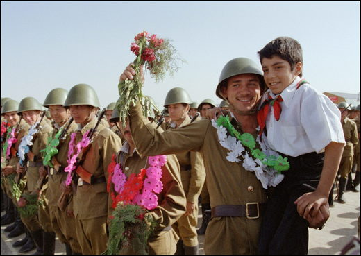 Red Army soldier holding an young Afghan pioneer